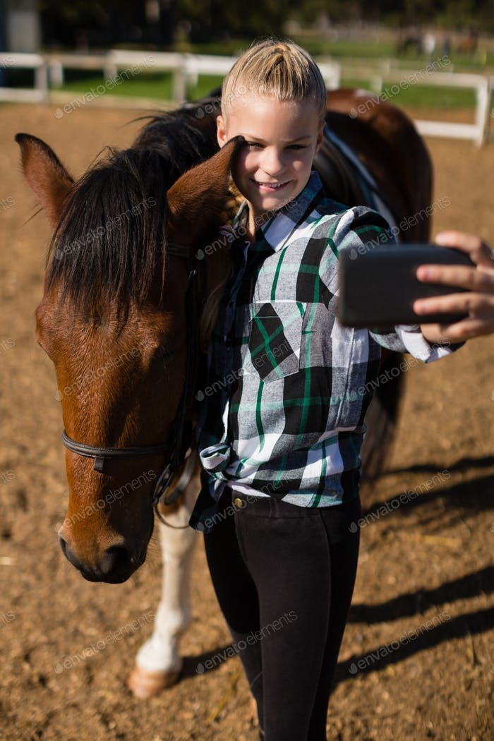 Girl taking a selfie with horse