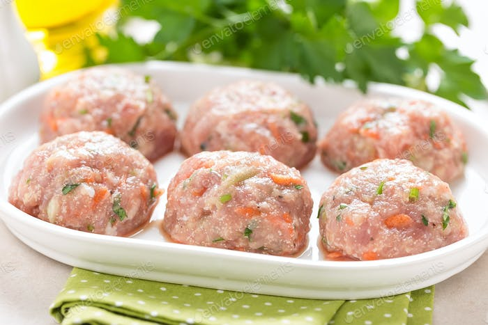 Raw meatballs on white plate, cooking in kitchen