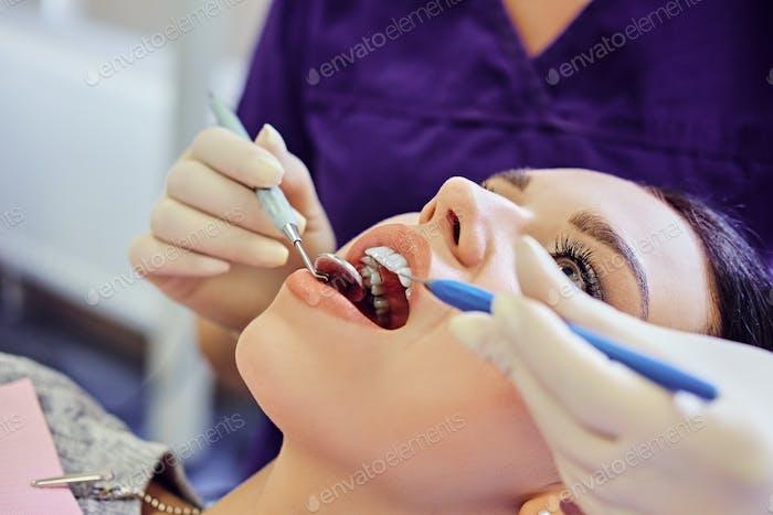 Zahnarzt untersucht weibliche Zähne in der Zahnmedizin.