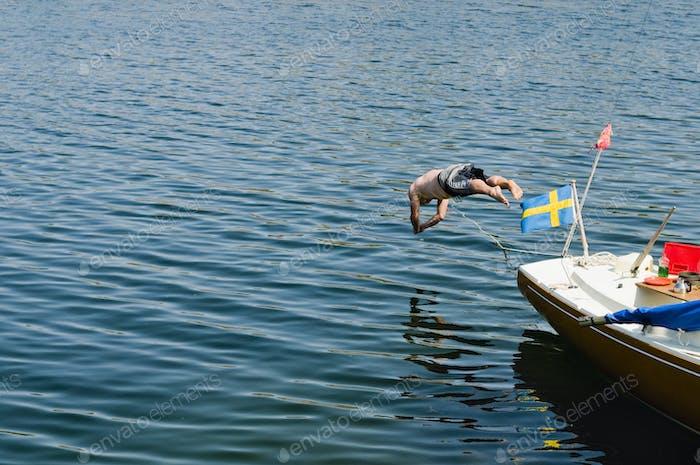 Shirtless man jumping into sea