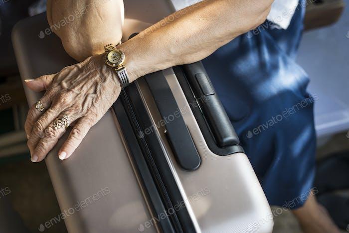 Senior Frau wartet mit ihrem Gepäck in einem Hotel