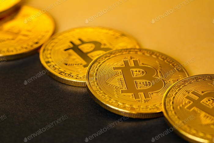 Closeup Of Shiny Bitcoin Crypto Currency Coins on Black and Yellow