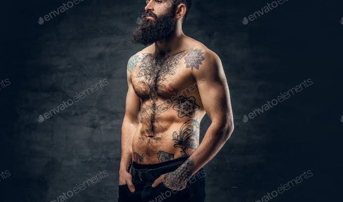 Bearded male with tattooed torso posing over dark grey backgroun