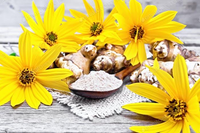 Flour of Jerusalem artichoke in spoon on board