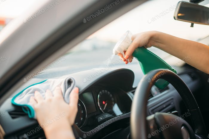 Female person polishes the dashboard of the car