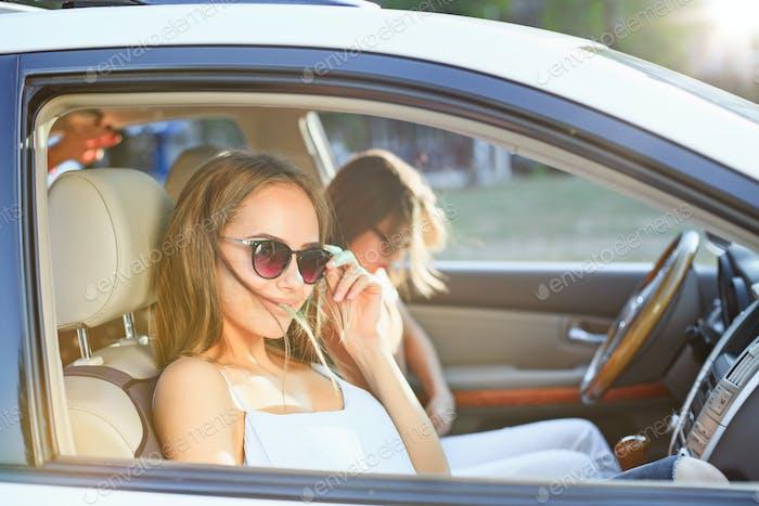 Die jungen Frauen im Auto lächelnd