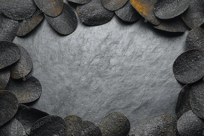 Black potato chips on dark slate rock background