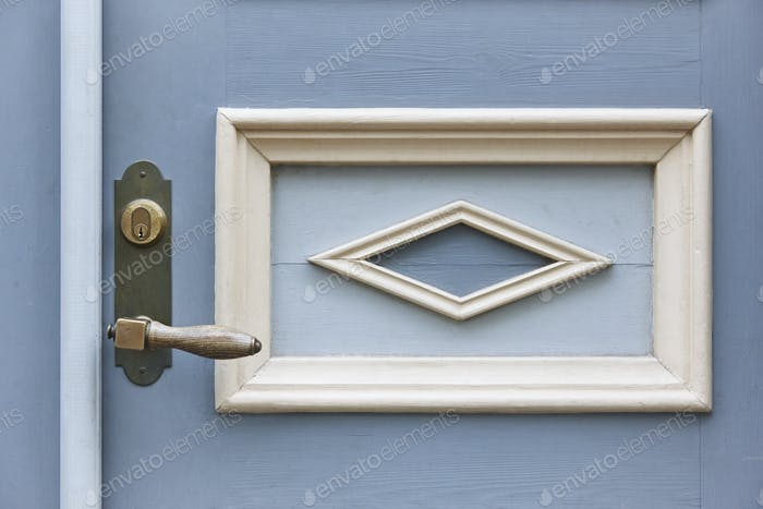 Classic doorknob on a vintage blue wooden door. Decoration. Horizontal