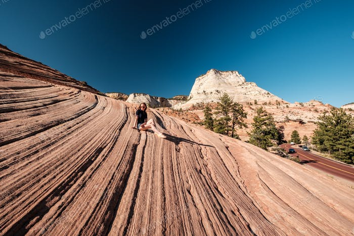 Woman sitting on rock formation in Utah, USA