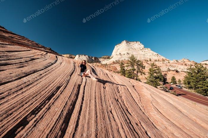 Frau sitzt auf Felsformation in Utah, USA
