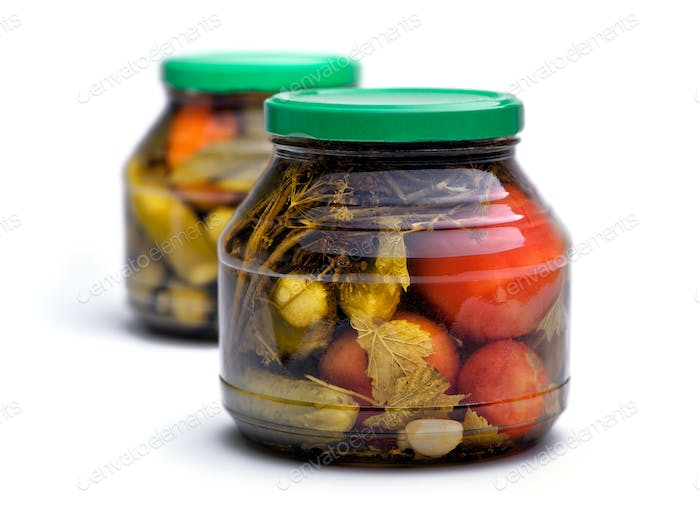 Pickled cucumbers and tomatoes in a glass jar