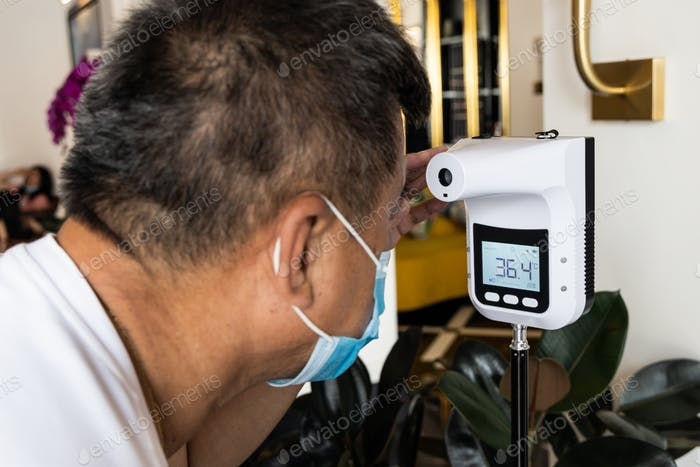 Asian man checking forehead temperature using infrared thermometer before enter establishment