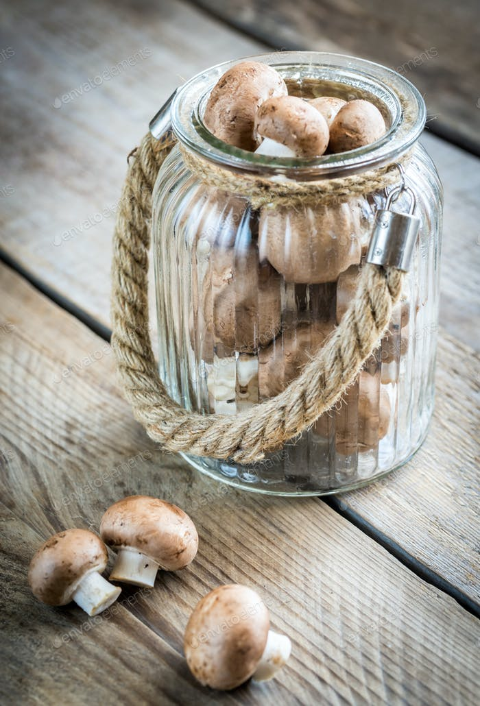 Brown champignon mushrooms on the wooden background