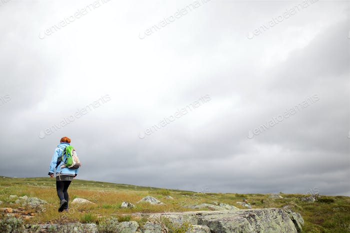 behind woman hiking gray sky