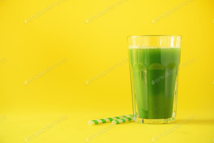 Glass of green celery smoothie on yellow background. Banner with copy space. Fresh juice for detox