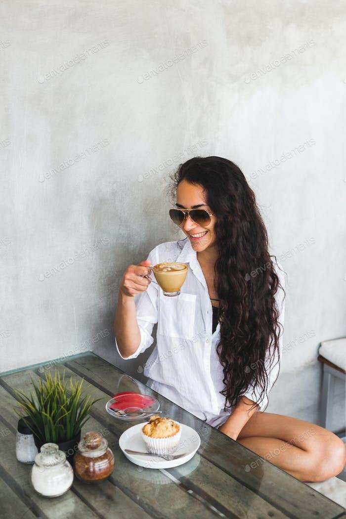 Mujer joven morena beber café en el moderno café loft con paredes de cemento