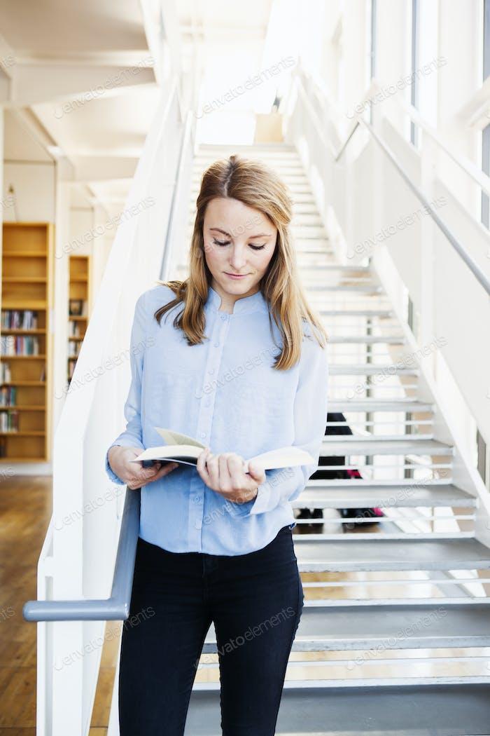 Junge Frau Buch lesen, während sie auf Stufen in der Bibliothek stehen