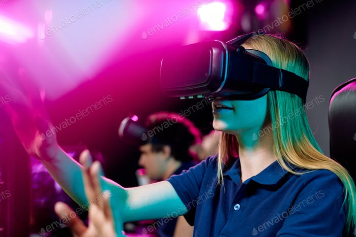 Blond girl in vr goggle touching virtual display during cybersports video game
