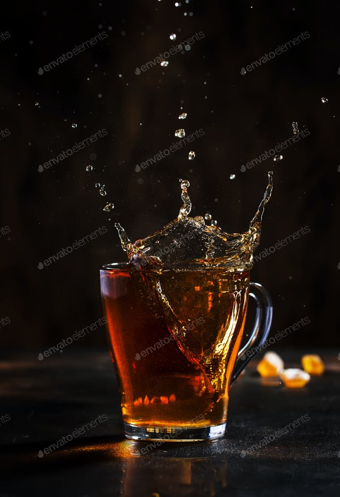 Splash in glass cup of black tea