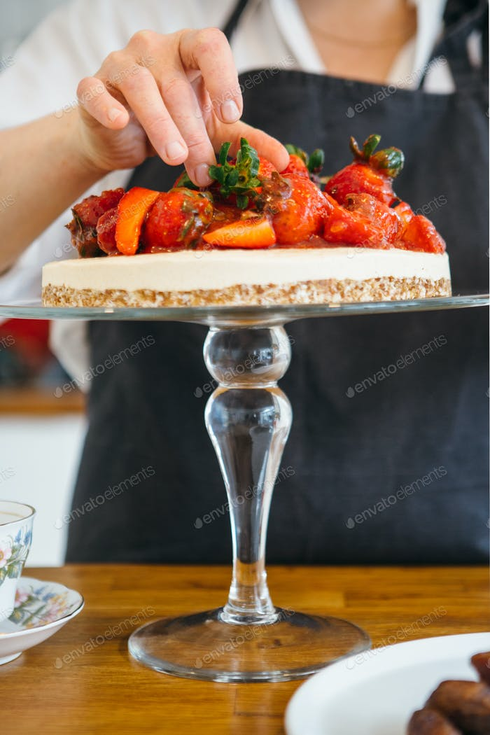 Confectioner decorating cake with berries