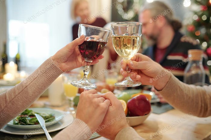 Hands of young couple clinking with glasses of wine during festive toast