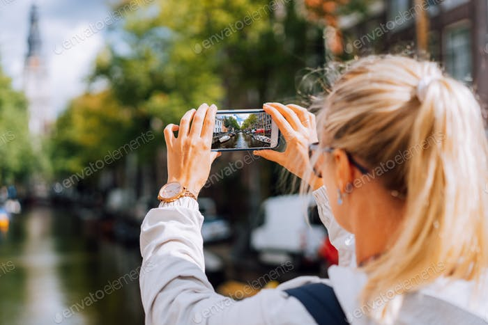 Blonde Woman tourist taking a photo of famous Soutern church (Zuiderkerk) and canal in Amsterdam on