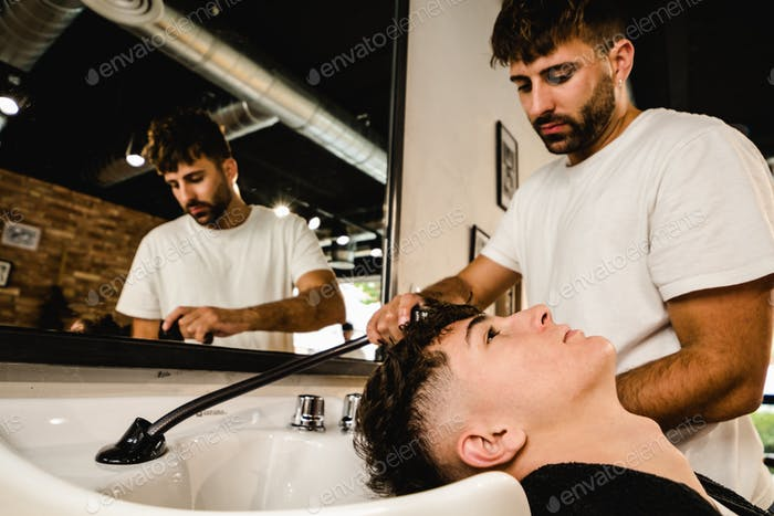 Man getting his hair washed by professional hairstylist