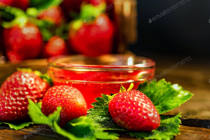 Fresh strawberries with leaves and jam close