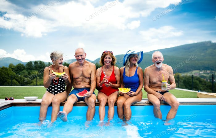 Group of cheerful seniors sitting by swimming pool outdoors in backyard