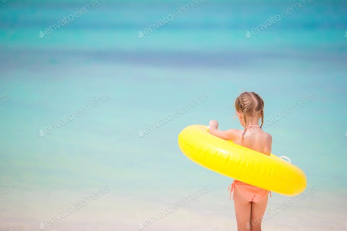 Adorable girl with inflatable rubber circle going to swim