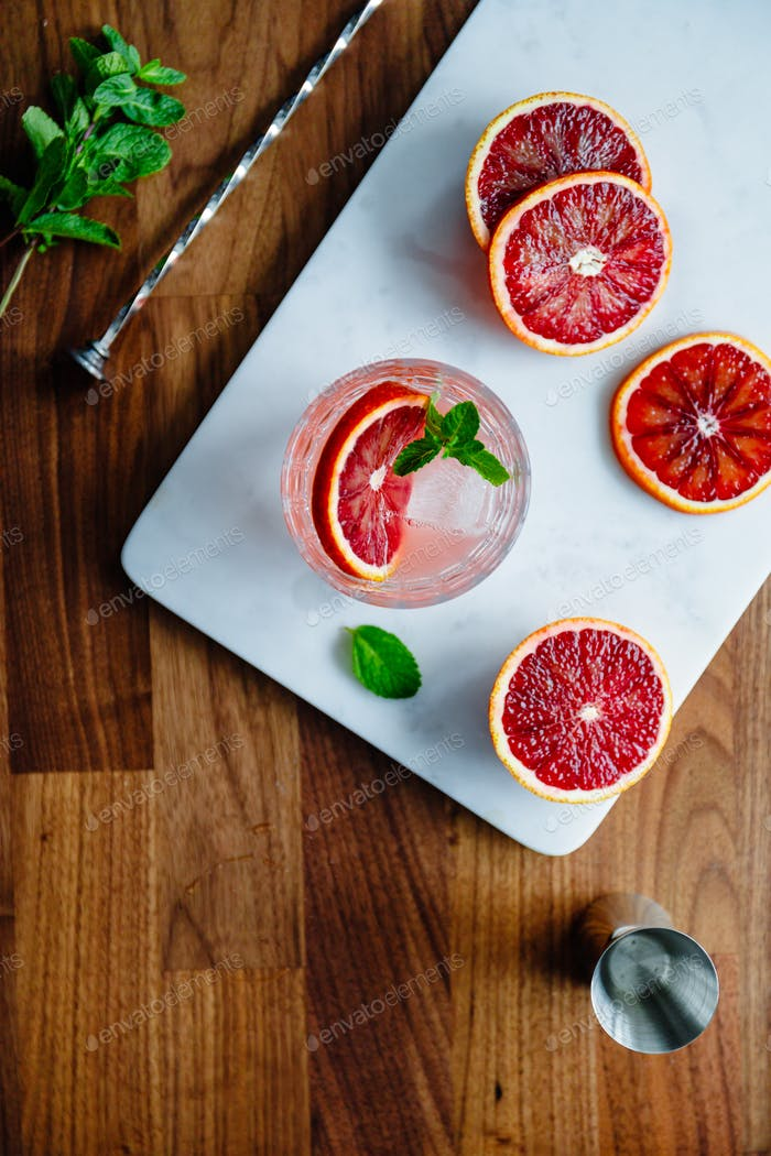 Refreshing cold summer cocktail with blood orange and mint on a marble tray.