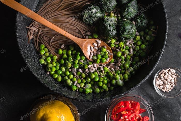 Buchweizennudeln in einer Pfanne, gefrorene Erbsen und Spinat, Chilis und Samen in einer Schüssel