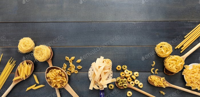 Pasta assortment on blue background, top view. Cooking italian cuisine concept