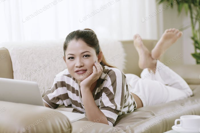 Girl with laptop resting on sofa