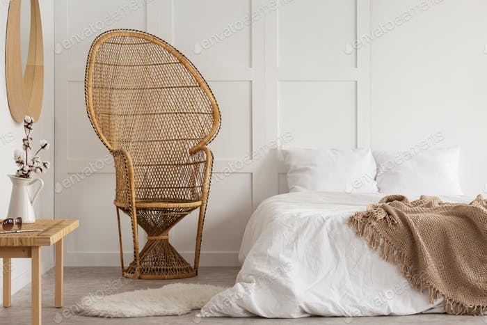 Flowers on wooden table next to rattan chair in white bedroom in