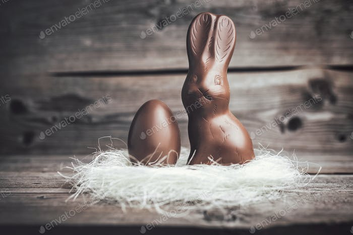 Chocolate Easter bunny and egg on wooden backround