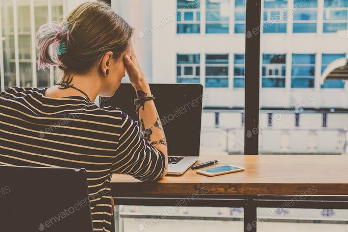 Back side of Depressed Hipster young Woman freelancer thinking about her job