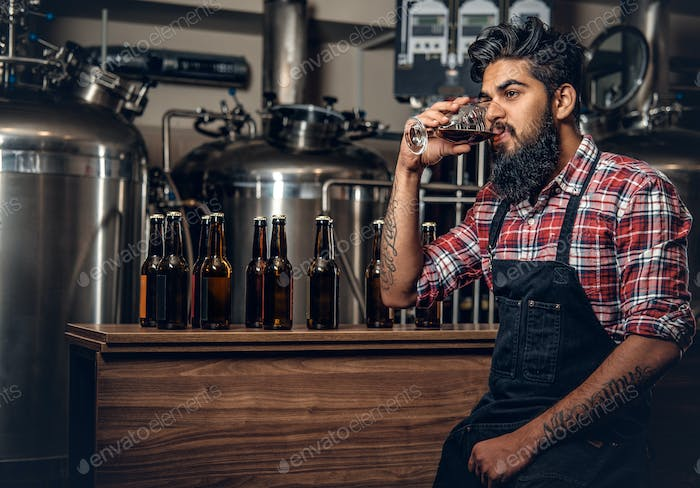 Indian male manufacturer tasting craft beer in the microbrewery.