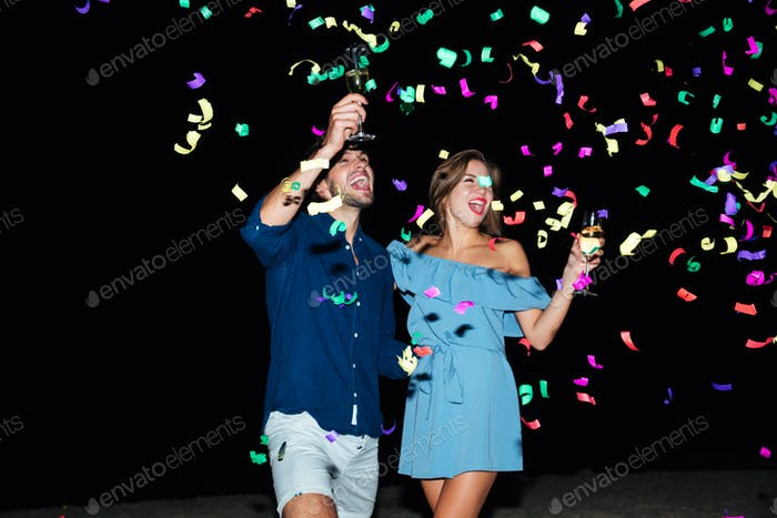 Couple drinking champagne and celebrating at night