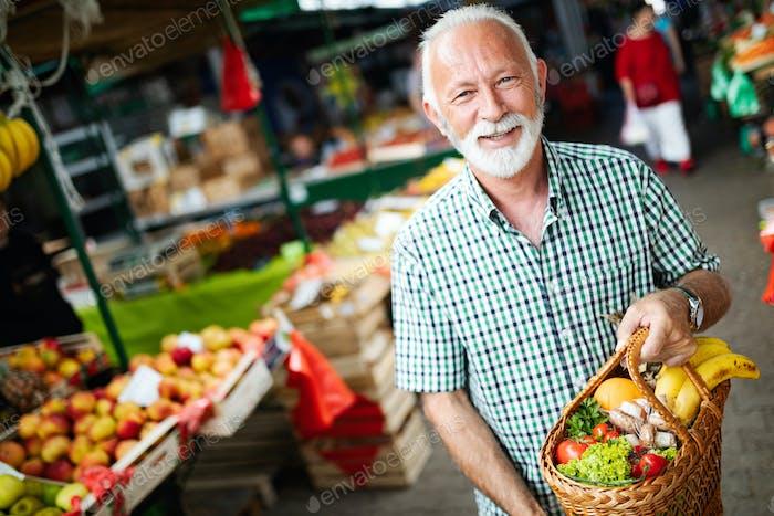 Ältere glückliche männliche Käufer halten Korb mit Obst und Gemüse