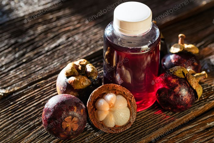 Fresh Mangosteen fruit and drink in bottle on wooden background