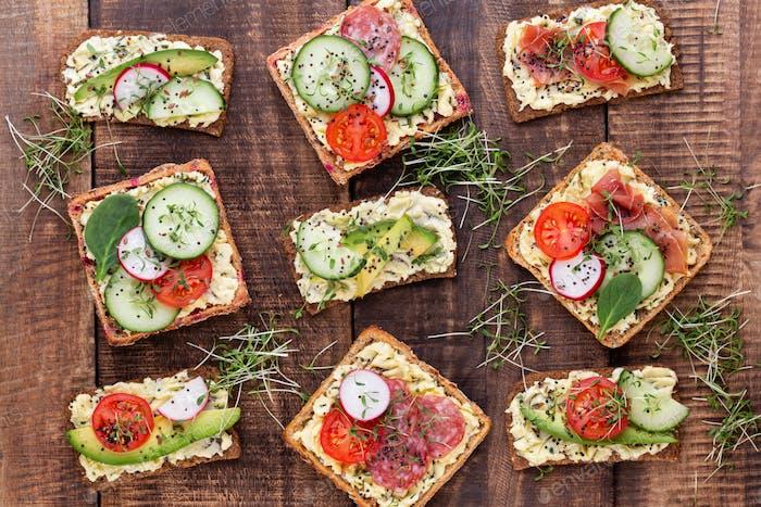 Sandwiches mit Frischkäse, Gemüse und Salami.