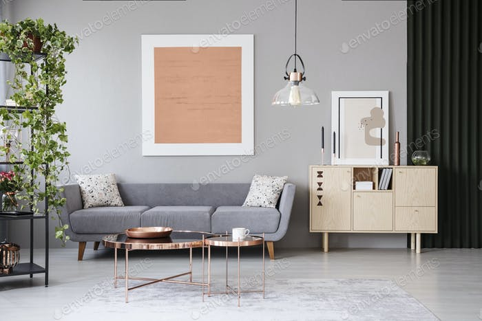 Copper tables in front of grey couch in modern apartment interio