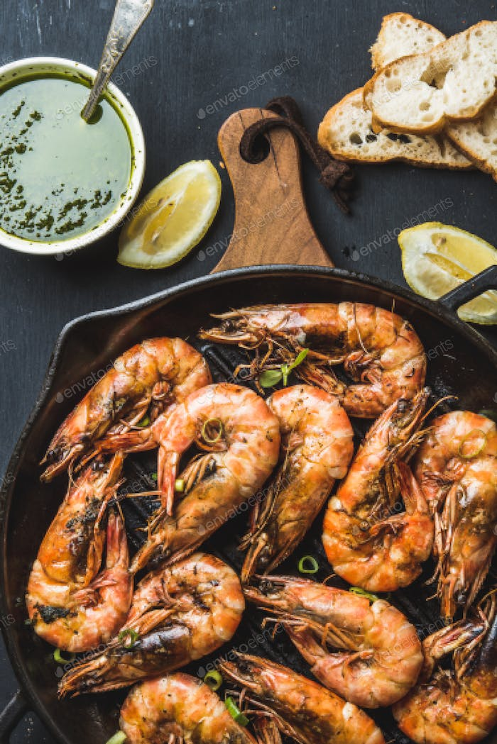 Roasted tiger prawns in iron pan on wooden board