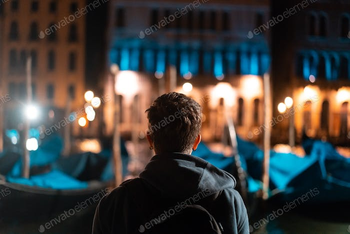 Young handsome guy walks alone by venice at night