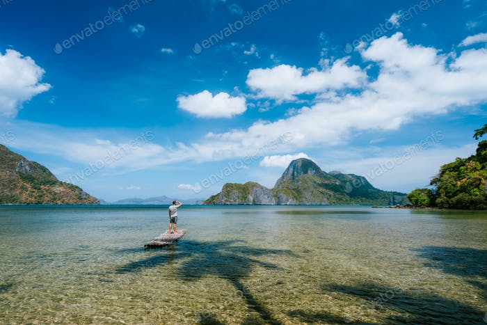 Man on bamboo float in shallow lagoon with panoramic view of shallow lagoon and Islands in Cadlao