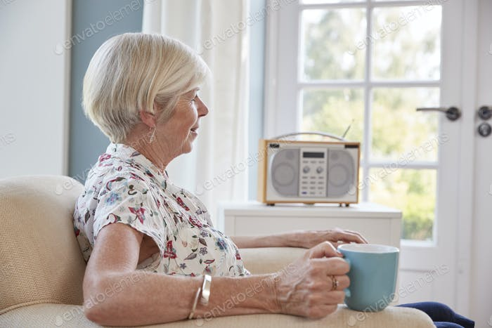 Senior woman drinking tea and listening to radio at home