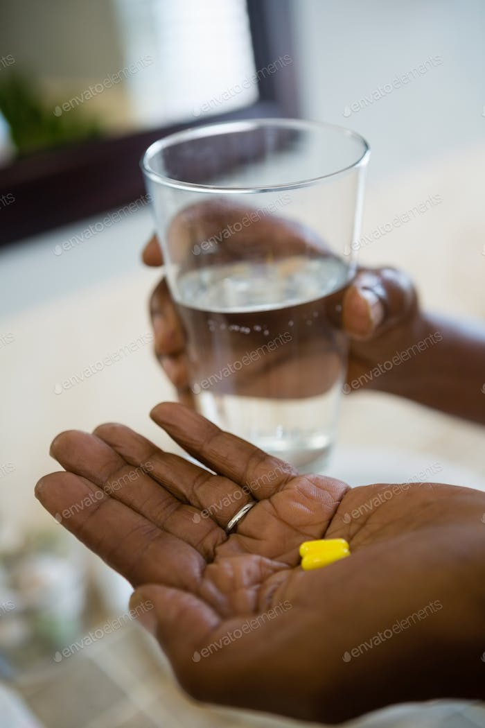 Cropped hands of person holding medicines and drinking water