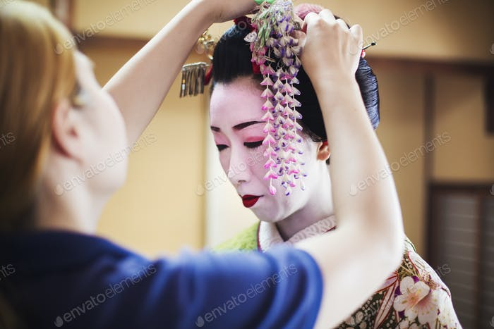 A geisha or maiko with a hair and make up artist creating the traditional hair style.