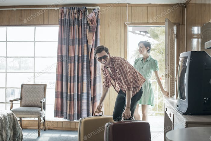 A young couple arriving in a motel room.